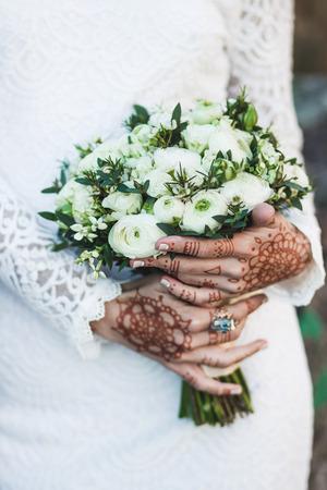 uñas pintadas: Agradable bouquet nupcial en la mano de la novia con tatuaje mehendi