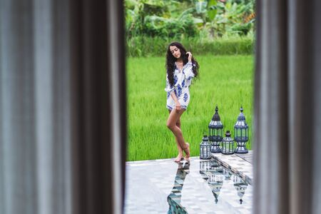 field mint: Woman resting in a beautiful hotel in the nature of rice fields in Bali Stock Photo