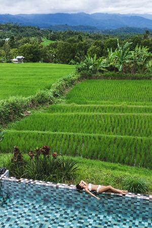 Young slim girl relaxing near luxury pool in Bali rice fields