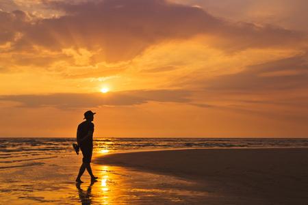 Man walking along the beach at sunset 版權商用圖片 - 66272921