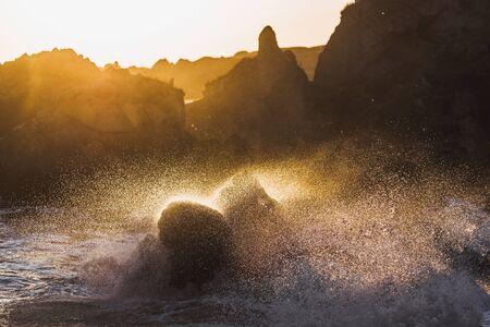 waves crashing: Waves crashing on rocks in sunlight