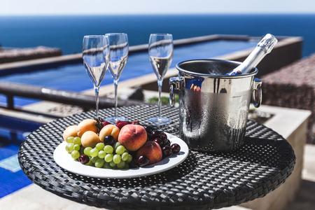 Frutas frescas y champaña fría junto a la piscina Foto de archivo