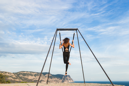woman practicing fly dance yoga poses in a hammock on the coast with views of aerial acrobatics stock photos  royalty free business images  rh   123rf