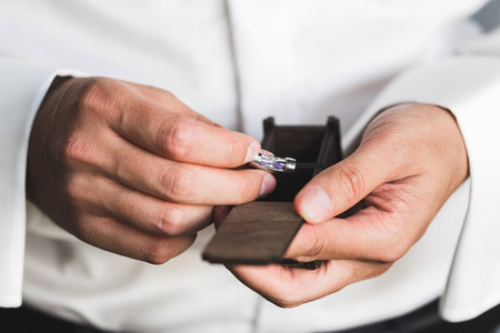 Preparations for the wedding, the groom wears cufflinks Stock Photo