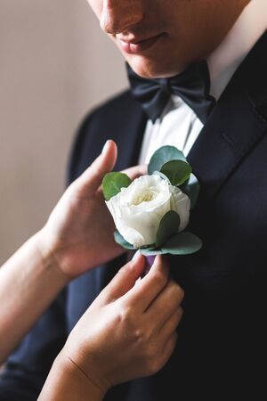 Preparations for the wedding, the bride helps the groom to wear boutonniere Stock Photo