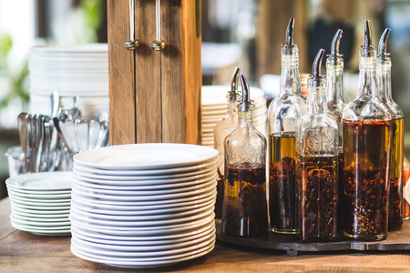Kitchen set in restaurant, cutlery, plates and various types of olive oil Stock Photo