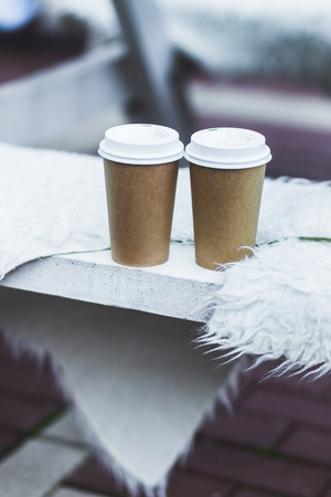 Two cup takeaway hot drink on bench seat covered with natural wool for warmth in winter