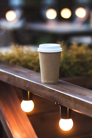 Cup takeaway coffee on cafe veranda with bokeh lights
