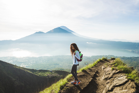 Beautiful woman at the top of Mount Batur, Bali, Indonesia. Mountain hiking at sunrise
