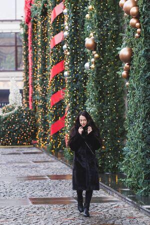 visone: donna felice a piedi in un cappotto di visone nero in città, splendidamente decorato per il nuovo anno Archivio Fotografico