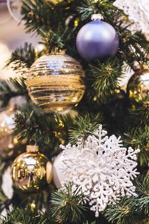 Beautiful shiny New Year decorations on Christmas tree with white showflake Stock Photo