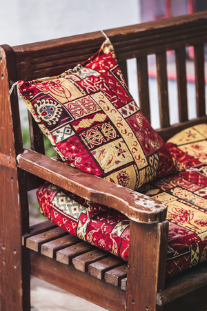 Traditional oriental decoration cafe, colorful pillows with handmade ornament, wooden bench