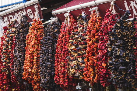 Dried fruits and vegetables sold in the market, hanging on the counter large bundles