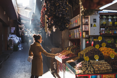 Woman chooses in the market nuts and dried fruit, the buyer tries goods at Grand Bazaar Istanbul