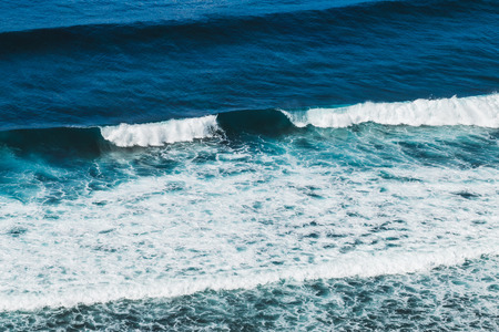 Ocean view from cliff coast, Bali sea landscape, look down from the height, surfing wave from above, Bali sea and surfing, high cliff and sea, jumping from cliff Stock Photo