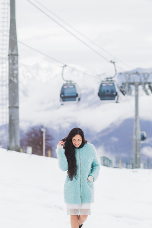 ski walking: Beautiful woman in blue coat walking at a ski resort in the snow. Modern ski lifts on background