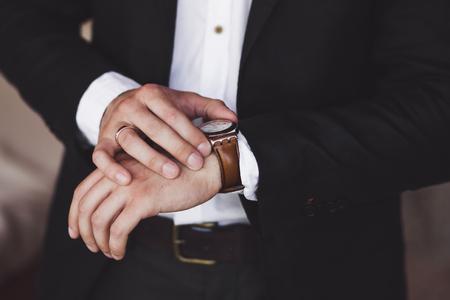 Mężczyzna w czarnym garniturze nosić nowe zegarki. Luksusowy styl