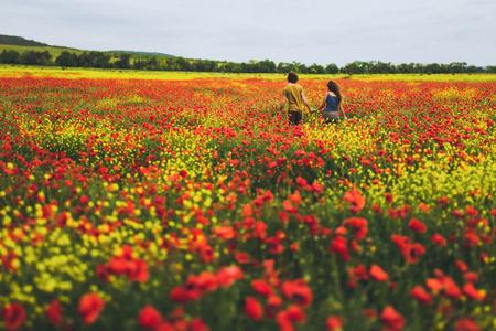 Jeune couple heureux avec des cheveux bouclés, appréciant dans le champ de floraison rouge et jaune vif de coquelicots au printemps Banque d'images