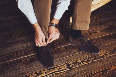 reparations: Groom reparations for the wedding. Wearing brown leather shoes and tying shoelaces