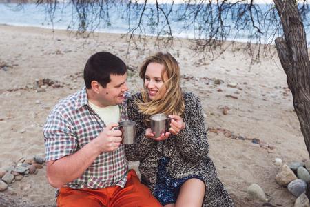 cocoa beach: Happy couple drinking cocoa with marshmallows outdoors at the beach Stock Photo