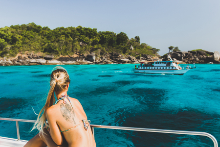Blonde woman with tattoo on back relaxing on luxury yacht with view of paradise tropical island with turquoise water Stock Photo