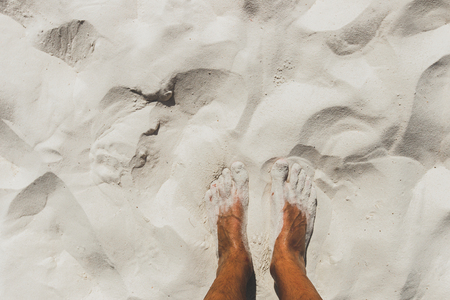 Tanned male legs on tropical beach with white sand. Paradise island