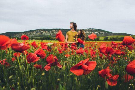 봄에 양귀비의 밝은 빨간색과 노란색 꽃이 만발한 필드에서 즐기는 곱슬 머리와 젊은 행복 한 커플