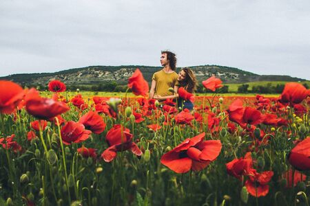 Young happy couple with curly hair enjoying in bright red and yellow blossoming field of poppies in spring