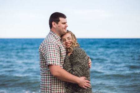 Man embraces and warms his girlfriend near sea. Couple portrait