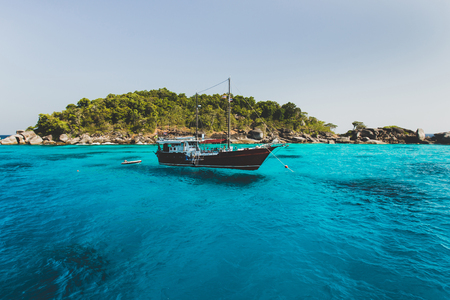 Tourist diving boat near island shore with turquoise clear transparent water. Idyllic view of Similan Islands