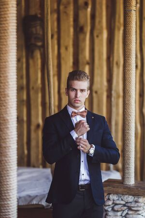 Portrait of elegant handsome man in black suit and bow-tie. Male fashion model