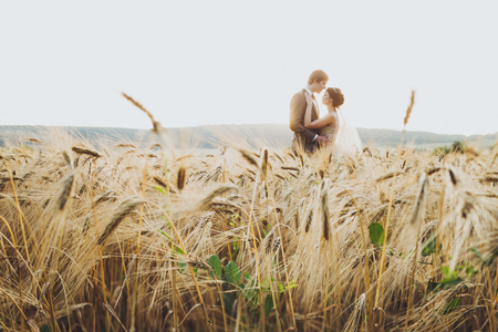 Loves couple in wheat field in sunlight. Romantic feelings at sunset