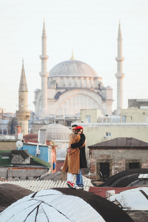 Couple in love standing on roof with view of Blue Mosque at background. Old Istanbul Sultanahmet