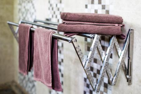 Set of clean hotel towels in bathroom on metal Sliding drier.