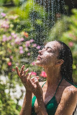mujer bañandose: Mujer que toma la ducha afuera en jardín tropical tropical de Bali con muchas flores. Salpicaduras frescas de agua limpia. Spa de lujo Foto de archivo