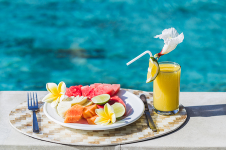 White plate with fresh fruit and juice with slice orange. Healthy breakfast on poolside in hotel in summertime. Plate with papaya, pineapple, watermelon, lime.