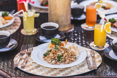 Traditional indonesian breakfast nasi goreng with bali kopi on white plate and silver cutlery on tray.  Table with different meals and fresh juices Stock Photo