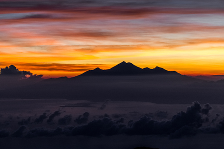 View of Rinjani peak from top of Agung volcano in Bali at sunrise summit. Sunrays and colorful sky, panoramic landscape, Agung trekking