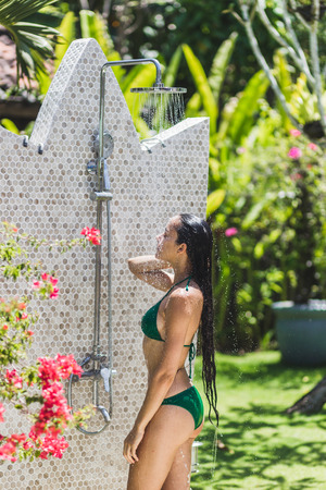 Woman taking shower outside in tropical green Bali garden with a lot flowers. Fresh splashes of clean water. Luxury spa