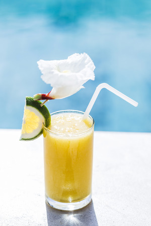 papaya flower: Fresh cold fruit juice on poolside. With straw, slice of lime and tropical flower