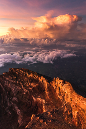 Crater rim of mount Agung in Bali at sunrise summit. Above the clouds, colorful landscape. First rays of rising sun in orange color. Top of Agung Volcano Stock Photo