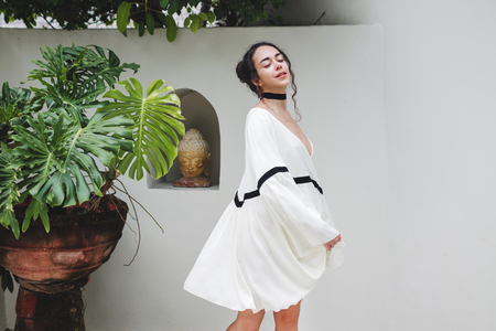 kuta: Asian woman with black curly hair enjoying in private villa in Canggu. Wearing white light tunic, barefoot. Casual style, tropical garden. Sunny weather