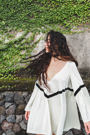 Woman with long curly hair in white light dress. Wind in hair