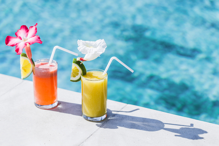 papaya flower: Two glasses of fresh cold fruit juice on poolside. With straw, slice of lime and tropical flower Stock Photo
