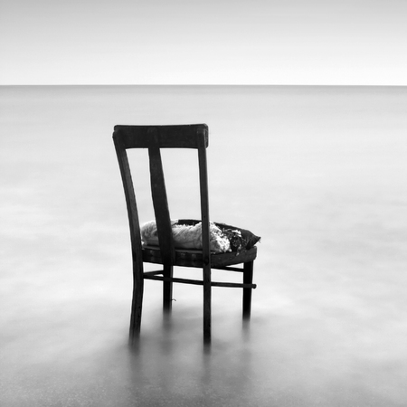 Conceptual landscape with long exposure. Black white minimalism, old chair in water. Place for advertising or text. Melancholy mood Stock Photo
