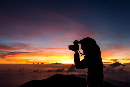 Man taking photo of amazing colorful sunrise at top of Agung Volcano in Bali. Multicolor cloud pattern at background, space for text and sign. Colorful sky Stock Photo