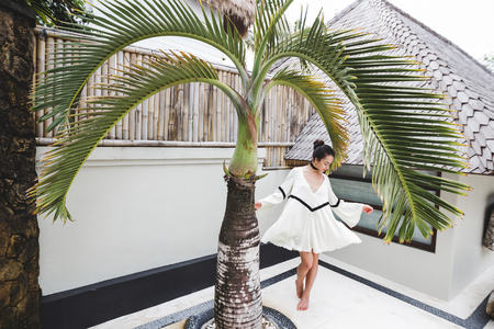 kuta: Woman in white tunic in tropical garden with palm tree and white background. Fashion shoot at private villa. Beige dress, barefoot