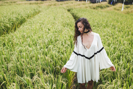 Young woman in white tunic in rice fields Bali in Tegallalang. Rustic Ubud village landscape outside. Fashion style, curly hair, light dress