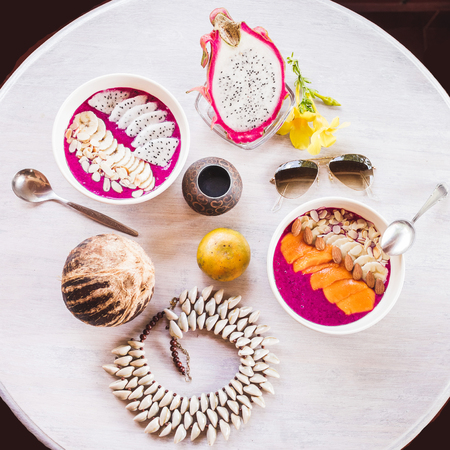 Healthy and tasty fresh breakfast on vintage round table served with sliced mango and dragon fruit, fresh papaya, coconut, smoothie. Lay flat in tropical colors with sunglasses, flowers, bijou and food, view from above