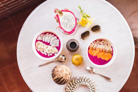 Sana e gustosa colazione fresca sul tavolo rotondo vintage servito con fette di mango e frutta drago, papaia fresca, cocco, frullato. Distesi piatti in colori tropicali con occhiali da sole, fiori, bijou e cibo, vista dall'alto